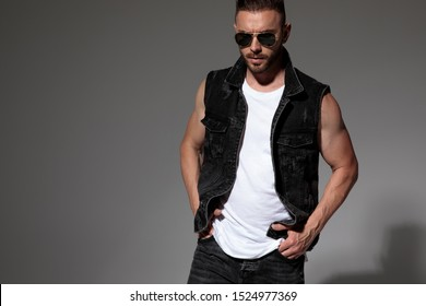 Tough man posing with both hands in his pockets while wearing sunglasses and a black jeans vest, standing on gray studio background