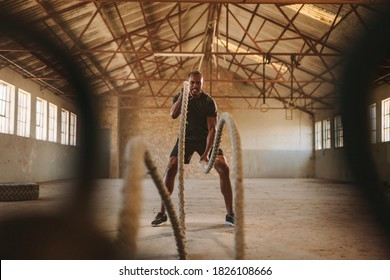 Tough man working out in training gym made inside old factory. Fitness man exercising with battle rope in abandoned warehouse.