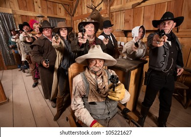Tough men and women pull out their weapons in a saloon