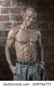 Tough muscular senior African American man with his shirt off dramatically lit against a brick wall