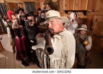 Tough old west desperado and group point their weapons in a bar