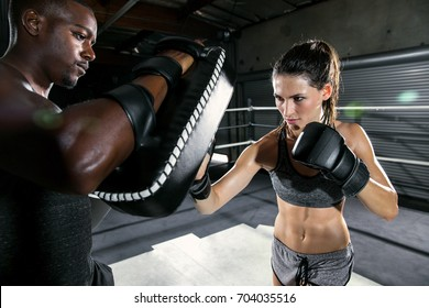 Tough physical female fighter exercising with african american trainer in coed boxing gym