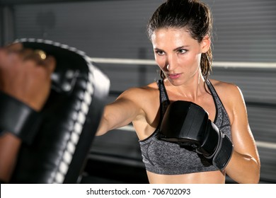 Tough resilient motivating woman at mixed martial arts gym throws a strike at practice gloves