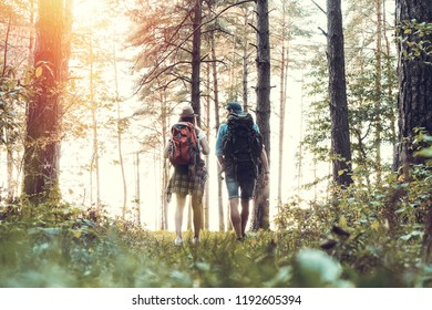Tough route. Beautiful young couple hiking together in the woods while enjoying their journey