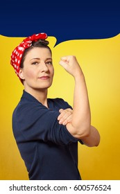 Tough and self-confident woman with a clenched fist rolling up her sleeve, empty speech bubble with text space, tribute to american icon Rosie Riveter