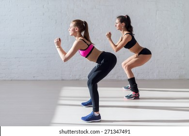 Tough stamina training for two young stunning fitness models doing squats together indoors.