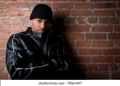 Tough street guy with his arms crossed, leaning against the brick wall.
