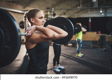 Tough woman with thick muscular arms pulling up large barbell in fitness training class with other adults and black floor mats indoors