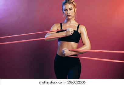 Tough woman using resistance bands in her exercise routine. Female athlete exercising with resistance band against colored background.