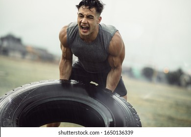 Tough young male athlete doing a tire flip exercise in the rain. Muscular man doing cross training outdoors on field.