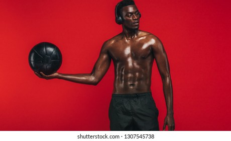 Tough young man with muscular physique holding a medicine ball against red background and looking away. African american man exercising with a fitness ball.