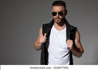 Tough young man pulling and adjusting his jeans vest while wearing sunglasses and standing on gray studio background