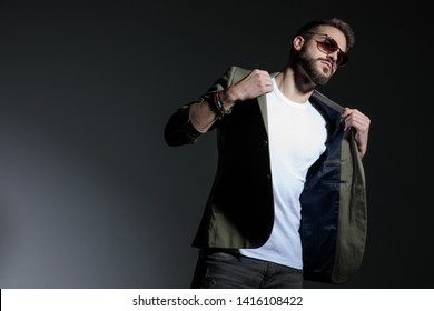 Tough young man pulling his jacket's collar and confidently looking to the side while wearing sunglasses and standing on gray studio background