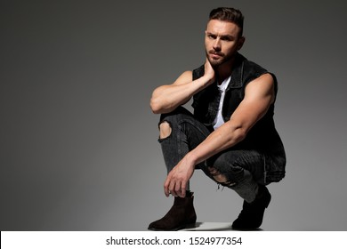 Tough young man touching his neck and squatting while wearing jeans and a black jeans vest on gray studio background