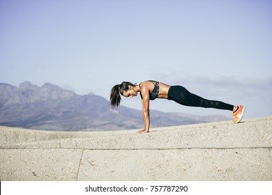 Tough young woman doing pushups outdoors. Fitness female exercising in morning.