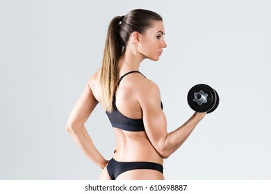 Tough young woman standing on grey background. Muscular female doing exercise.