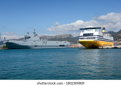 TOULON, FRANCE - JULY 19, 2020. The Corsica Ferrie and a French National Navy ship. In the background, the mountains.