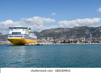 TOULON, FRANCE - JULY 19, 2020. The Corsica Ferries ship provides crossings to Corsica and Sardinia. In the background, residential buildings and the mountains.