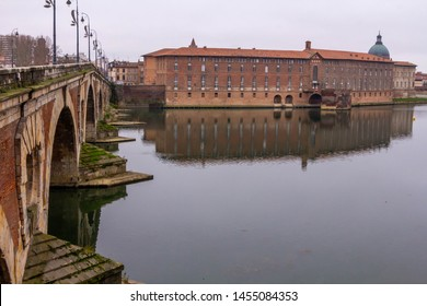 The Toulouse Bridge (Pont Neuf) in winter, with perfect reflections of the arches on the river