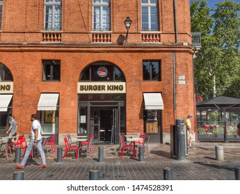 Toulouse, France, 08/05/2019: facade of Burger King store on downtown historical Toulouse, pedestrian walking in front