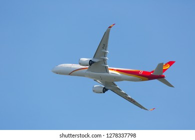 Toulouse / France - 12.17.2018. Blagnac Airport, Airbus Plant. Modern passenger aircraft Airbus A350 XWB of Hong Kong Airlines is climbing in the blue sky. Airplane bottom view.