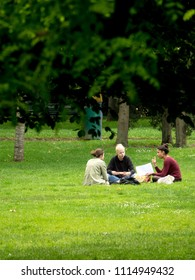 TOULOUSE ,FRANCE- 14 Jun 2018: Students take advantage of the weather to have lunch on the grass of a public garden and revise their courses for the baccalaureate.
