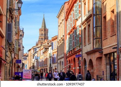 TOULOUSE, FRANCE: APRIL 01, 2018: People walking in the street in te city of Toulouse, with San Sernin basilica in the background