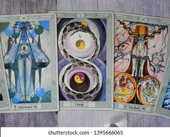 Toulouse, France - April 27, 2019: Three cards of the Major Arcana of an elaborate Tarot deck: the Devil, Change and Adjustment spread on a gray-blue wooden background - top view of card reading