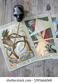 Toulouse, France - April 27, 2019: Pair of cards of Major Arcana of an elaborate Tarot deck: the Hermit and Death spread on a gray-blue wooden background - top view of card reading