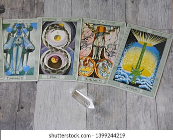 Toulouse, France - April 27, 2019: Several cards  of an elaborate Tarot deck spread on a gray-blue wooden background with a quartz crystal - top view of card reading