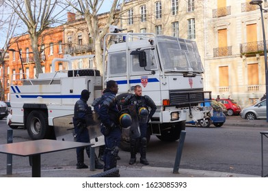 Toulouse, France - Jan. 2020 - Group of police officers from CRS units, in front of a riot truck featuring a water gun, roo bar and protection grids, during a manifestation against the pension reform