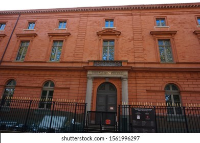 Toulouse, France - Nov. 2019 - Facade of the High Court brick building (Court of First Instance) at the back of the Palace of Justice, behind a cast iron gate with golden spearheads, Carmes District