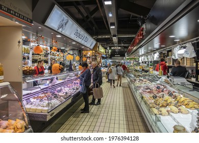 TOULOUSE, FRANCE - OCTOBER 25, 2019: Interior of Marche Victor Hugo - covered market, packed with local producers busily selling cheeses, fresh meats and fish, vegetables, fruit.