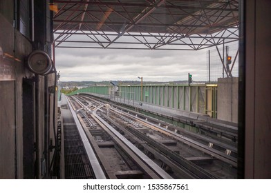 Toulouse, France -Sept. 2019- Railway tracks of the metro, with a switch point and railroad sign, at the viaduct of the station Jolimont, on line A, with a metal frame, hills of Balma in the backround