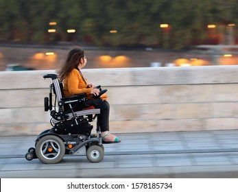 Toulouse, France - September 18 2018: fast ride on an electric wheelchair on the Pont-Neuve bridge over Garonne