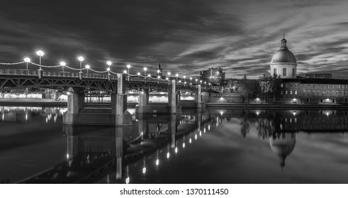 Toulouse,Aude/France November 2018 Pont Saint-Pierre and Chapelle Saint-Joseph de la Grave at night in black and white ,bridge and a chapelle at night, reflection in river water, clouds and city light