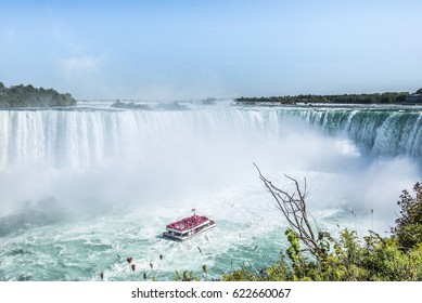 A tour boat loaded with tourists in red ponchos cruises towards to mist at the base of the Horseshoe Falls in Niagara Falls Ontario.