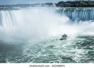 A tour boat sails in the frothy blue green water of the Niagara River toward the base of the Horseshoe Falls in Niagara Falls Ontario Canada.