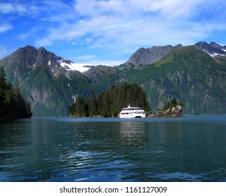 Tour boat stops to let visitors admire Entrance Island in Prince William Sound in Alaska.  Beautiful Chugach Mountainns and the Anderson Glacier form backdrop.