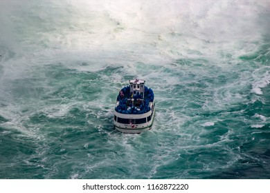 A tour boat travels away from the camera towards rough water. This was taken at Niagara Falls but the shot is a close up of the rear of the boat and the falls are not visible only the white waters.