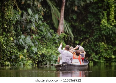 The tour guide shows tourists in a canoe the beauty of the nature at a river in the Tortugero National Park, Costa Rica.