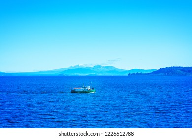 Tour steamboat crossing the deep blue waters of lake Taupo with Ruapehu mountains in the background on a beautiful sunny day. North Island Volcanic Plateau, New Zealand
