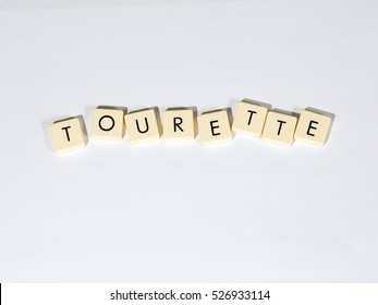 Tourette text on a white surface. Tourette Syndrome is one type of Tic Disorder. Tics are involuntary, repetitive movements and vocalizations.