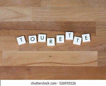Tourette text on a wooden surface. Tourette Syndrome is one type of Tic Disorder. Tics are involuntary, repetitive movements and vocalizations.