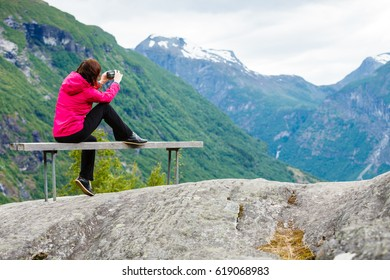 Tourism adventure and travel. Female tourist hiker sitting on bench in stone mountains taking photo with camera, looking at scenic view, Norway Scandinavia.