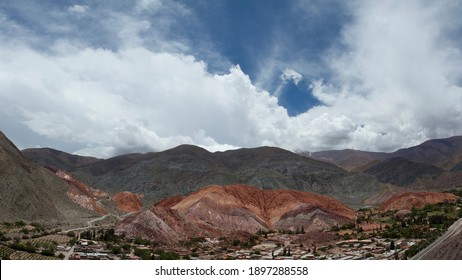 Tourism. Aerial panorama view of the popular landmark Seven Color Hill and Purmamarca village in Jujuy, Argentina. The colorful mountains and buildings under a beautiful sky.