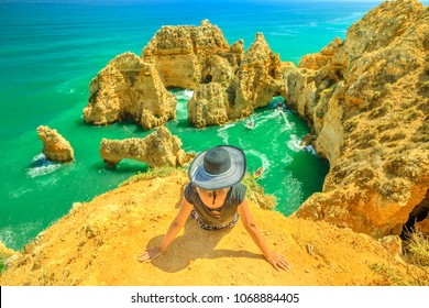 Tourism in Algarve. Summer holidays in Portugal, Europe. Lifestyle tourist sitting on promontory of Ponta da Piedade. Caucasian woman looking amazing views of iconic cliffs of turquoise sea of Lagos.