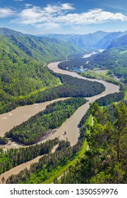 Tourism in Altay, Russia. View of the valley and the Katun River from the mountain. Spring view. Green forests and meadows and a beautiful sky.