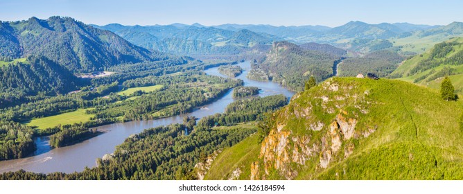 Tourism in Altay, Russia. View of the valley and the Katun River from the mountain. Spring panoramic view. Green forests and meadows and a beautiful sky.