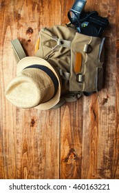 Tourism concept. Backpack, hat , binocular and old camera isolated on wooden background.